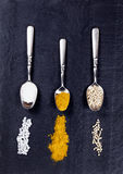 Spoons with a variety of spices spilled on natural black slate s. Overhead view of three old spoons containing various spices with trails on natural black slate stock images