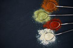 Spoons with various spices. On a dark background. Colorful mix of spice. Top view. Selective focus stock photos