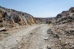 Spoor die rotsachtig dor woestijnlandschap doornemen in oude Namib-Woestijn van Angola stock fotografie