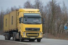 Spoor van VOLVO FH 13 440 met de drager van de opleggercontainer op de weg in de sombere Maart-dag Royalty-vrije Stock Afbeelding