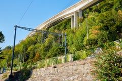 Spoorweg bij de voet van de berg die door een muur wordt gescheiden die door groen op de zomer wordt omringd royalty-vrije stock afbeeldingen