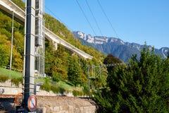 Spoorweg bij de voet van de berg die door een muur wordt gescheiden die door groen op de zomer wordt omringd royalty-vrije stock afbeelding