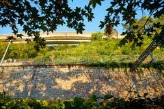 Spoorweg bij de voet van de berg door een muur wordt door groen op de zomer wordt omringd gescheiden die royalty-vrije stock foto