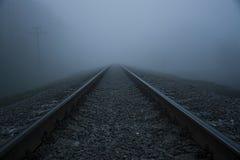 Spoorweg in de mist Dikke mistspoorweg stock afbeelding