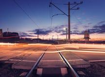 Spoorweg die met autolichten in motie bij nacht kruisen Royalty-vrije Stock Afbeelding