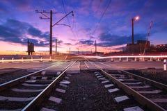 Spoorweg die met autolichten in motie bij nacht kruisen Stock Foto