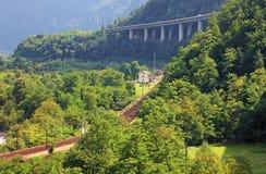 Spoorweg en hghway, Alpen. Royalty-vrije Stock Afbeeldingen
