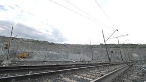 Spoorweg op achtergrond van open kuil Spoorweg die door mijnbouw met bevindend graafwerktuig op achtergrond overgaan royalty-vrije stock foto's