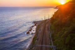 Spoorweg op zeekustbladeren op zonsondergang Stock Foto's
