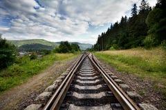 Spoorweg tegen Bergen en Mooie Hemel, dichtbij Bos Stock Fotografie