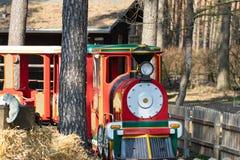 Spoorweg voor kinderen Een rode stoomlocomotief voor kleine kinderenaandrijving door een vrije tijdspark in het hout Spoorwegreis royalty-vrije stock foto