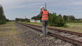 Spoorwegarbeider die dichtbij spoorweg lopen stock footage