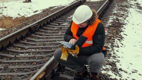 Spoorwegarbeider die documentatie controleren dichtbij spoorweg stock footage