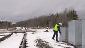 Spoorwegarbeider die elektrobijlagen controleren stock videobeelden