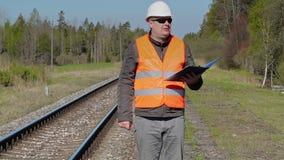 Spoorwegarbeider die en dichtbij spoorweg lopen schrijven stock footage