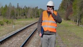 Spoorwegarbeider die en op slimme telefoon dichtbij spoorweg lopen spreken stock video