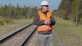 Spoorwegarbeider die en tabletpc loopt met behulp van dichtbij spoorweg stock footage