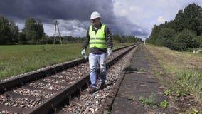 Spoorwegarbeider die met celtelefoon en regelbare moersleutel dichtbij spoorweg in langzame motie lopen stock footage
