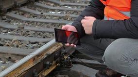 Spoorwegarbeider die tabletpc op spoorweg met behulp van stock footage