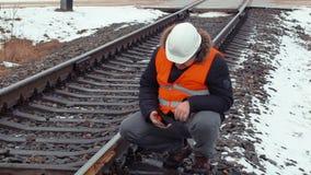 Spoorwegarbeider met de controlespoorweg van tabletpc stock video
