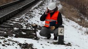 Spoorwegarbeider met documentatie die op slimme telefoon dichtbij spoorweg spreken stock videobeelden