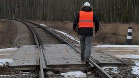 Spoorwegarbeider met documentatie en regelbare moersleutel dwarsspoorwegovergang stock videobeelden