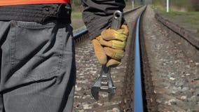 Spoorwegarbeider met regelbare moersleutel op spoorweg in de lente stock videobeelden