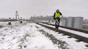 Spoorwegarbeider met waarschuwingsbord die op telefoon spreken en op spoorweg lopen stock video