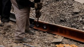 Spoorwegarbeiders die spoorspoor vastbouten stock footage