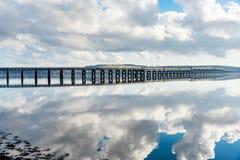 Spoorwegbrug over een brede rivier en een bewolkte hemel stock foto's