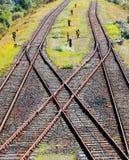 Spoorwegen die op grint in zonlicht kruisen Stock Afbeelding
