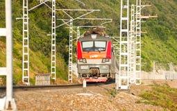 Spoorwegentrein op achtergrond van groene berghellingen Stock Foto's
