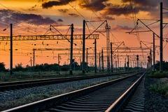 Spoorweginfrastructuur tijdens mooie zonsondergang en kleurrijke hemel, railcar en verkeerslichten, vervoer en industriële concep royalty-vrije stock afbeelding