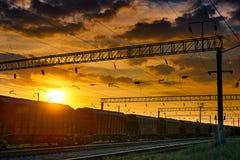 Spoorweginfrastructuur tijdens mooie zonsondergang en kleurrijke hemel, railcar voor droge lading, vervoer en industrieel concept royalty-vrije stock fotografie