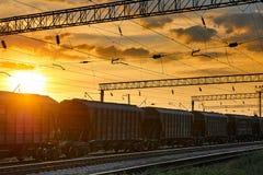 Spoorweginfrastructuur tijdens mooie zonsondergang en kleurrijke hemel, railcar voor droge lading, vervoer en industrieel concept stock afbeelding