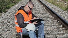 Spoorwegingenieur met documentatie op spoorweg stock footage