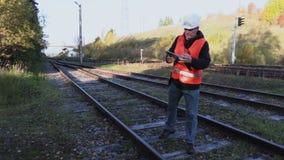 Spoorwegingenieur met documentatie op sporen stock videobeelden