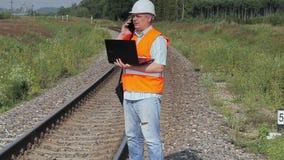 Spoorwegingenieur met PC op spoorweg stock videobeelden