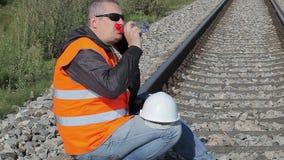 Spoorwegingenieur met smartphone en fles water stock footage