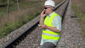 Spoorwegingenieur met smartphone en geld op spoorweg stock video