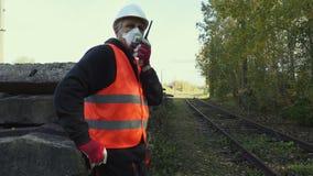 Spoorweginspecteur in het luchtmasker bij spoorweg stock footage