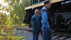 Spoorwegovergang De familie bevindt zich dichtbij de spoorweg en bekijkt de voorbijgaande locomotief Autumn Park, schilderachtig stock videobeelden