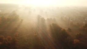 Spoorwegspoor bij zonsopgang in de mist Mening van de hommel
