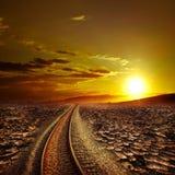 Spoorwegspoor die droogtewoestijn kruisen onder zonsonderganghemel stock foto