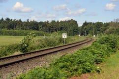 Spoorwegspoor met weiden, bomen en blauwe hemel Royalty-vrije Stock Foto's