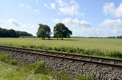 Spoorwegspoor op het Oostzeeeiland Usedom met weiden, bomen en blauwe hemel Stock Afbeeldingen