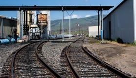 2 spoorwegsporen die binnen tot een lading het leegmaken faciliteit leiden royalty-vrije stock afbeelding