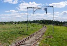 Spoorwegsporen die in de afstand naar het bos en het dorp in de zomerdag gaan Stock Foto