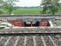 Spoorwegsporen door dorp en landbouwbedrijven stock afbeeldingen