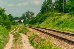 Spoorwegsporen en een weg lopende parallel royalty-vrije stock afbeeldingen